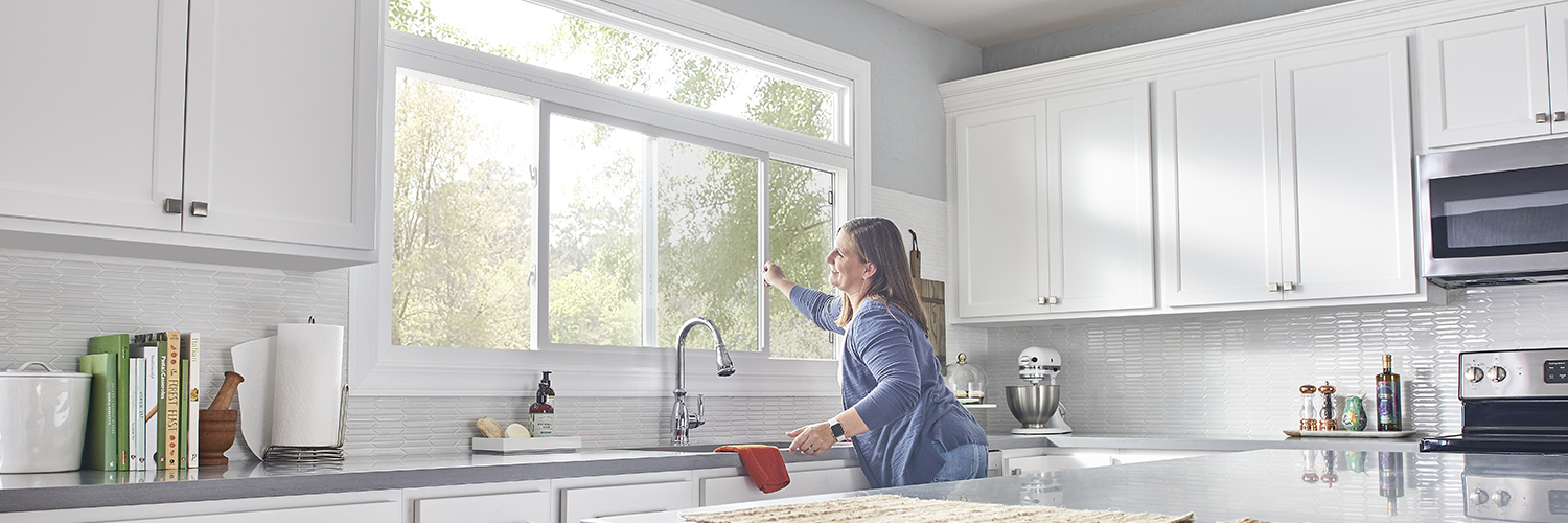 Woman opening vinyl slider window in kitchen